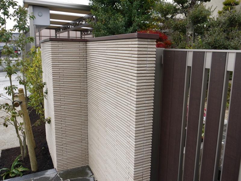 門塀の上に笠木を乗せると、落ち着いた雰囲気の門構えに。門扉と同素材でコーディネート。