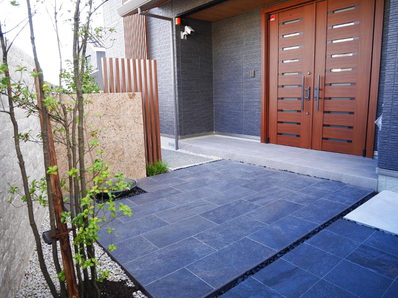 玄関前のスペース。磨き石の壁と水鉢で演出。
