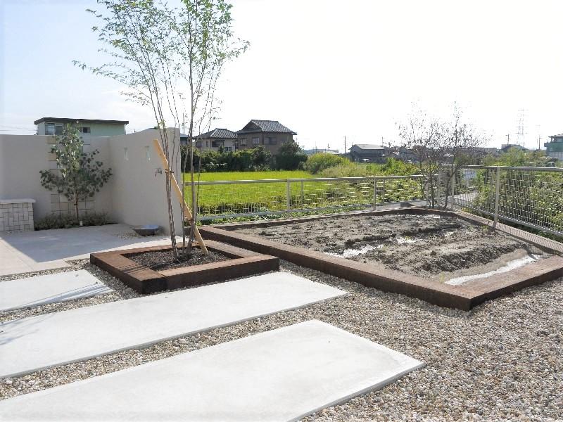 枕木で囲った花壇と菜園スペース。