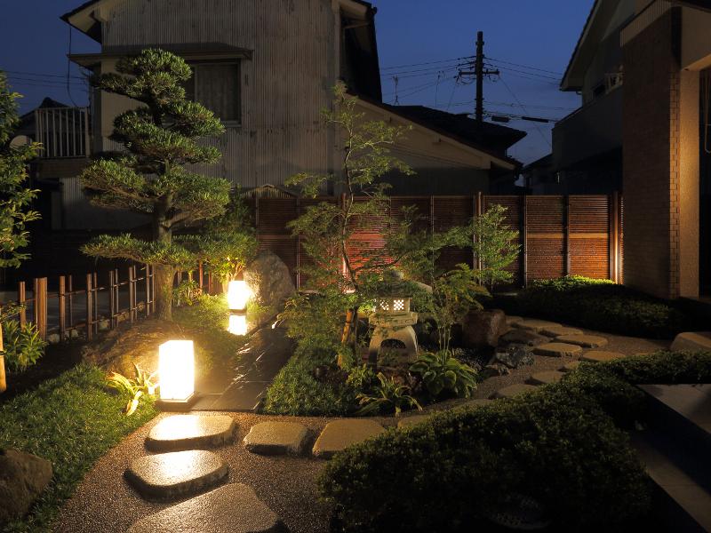 アプローチより夜の和庭園の風景。床の石張りや照明を回廊できるように配置。
