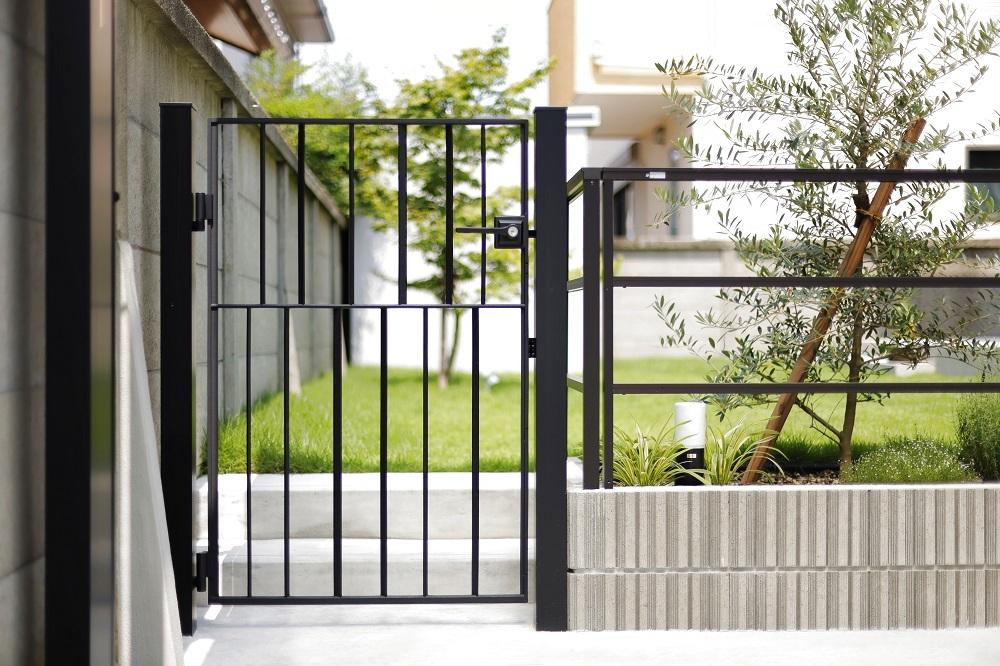 タテ・ヨコの異なるラインが織り成すシンプルモダンな雰囲気。インダストリアルなフェンス・扉とグリーンの親和性。