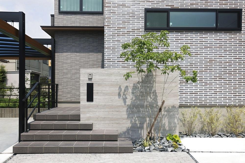 アプローチ階段は一段一段広がりを見せ、奥行き感を演出。植栽・景石・タイル・杉板フェンス・外壁の異素材の絶妙なカラーニュアンス。