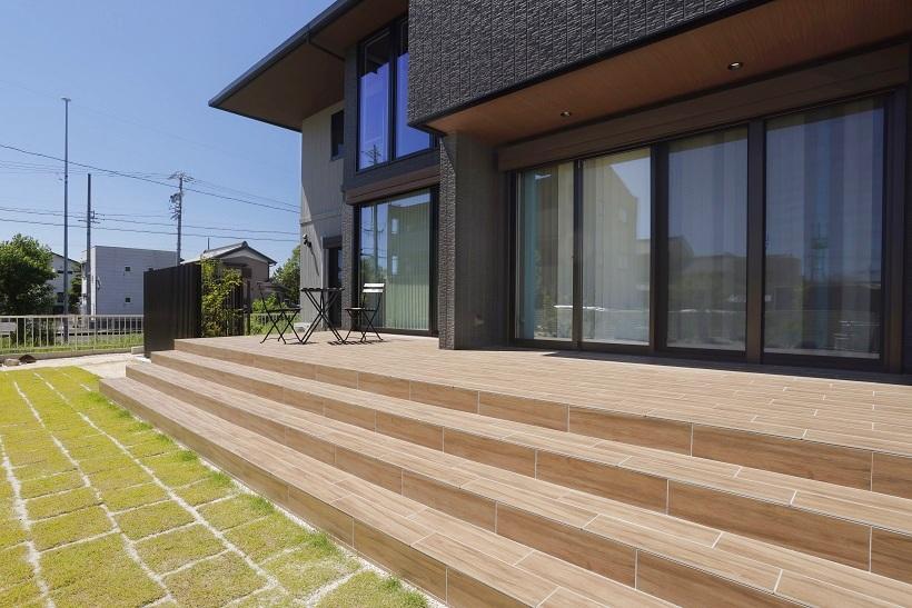 タイルデッキは掃き出し窓より更に幅を出し、走り回れる程の面積を。ゆるやかにステップ状になるナチュラルな木目調のタイルが豊かな芝とのグラデーションに。
