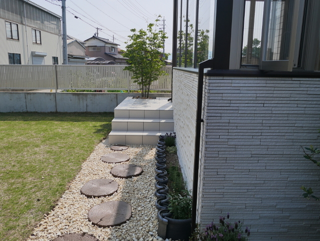 階段までのアプローチは、コンクリート製の平板です。本物の切り株のようです。